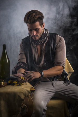 loner: Good Looking Young Man in Pirate Fashion Outfit Sitting and Looking at Gold in Hand