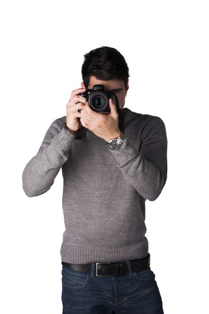 Handsome young man taking photo with professional photocamera, standing isolated on white photo