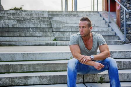 rubia ojos azules: Apuesto hombre rubio musculoso sentado en los escalones de la escalera en el establecimiento de la ciudad que mira lejos