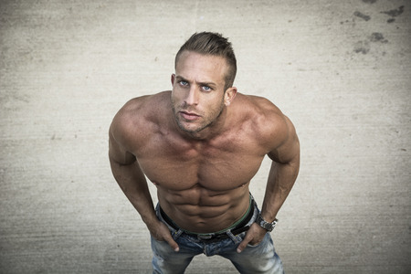 Shirtless muscular man shot from above, looking at camera, standing outdoor Stock Photo