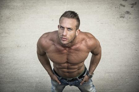 nudo maschile: Uomo muscolare senza camicia ripresa dall'alto, guardando a porte chiuse, in piedi all'aperto Archivio Fotografico