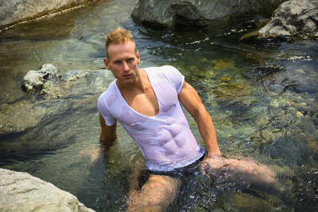 Handsome young muscle man sitting in water pond, wearing wet t-shirt looking at camera