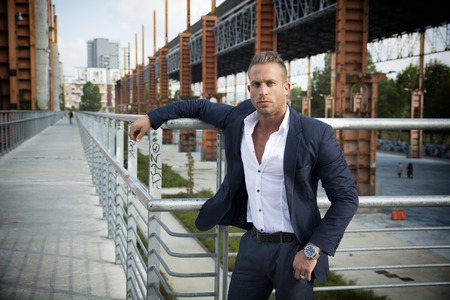 standing: Handsome muscular blond man standing in city setting or former industrial environment