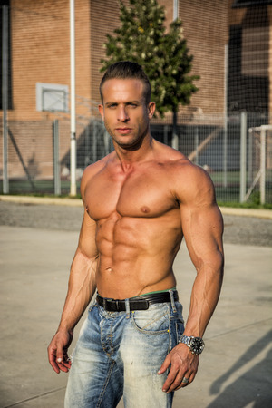 sin camisa: Handsome Muscular Hunk descamisado Hombre al aire libre en Ciudad Marco. Mostrando Cuerpo Sano Mientras que mira la cámara Foto de archivo