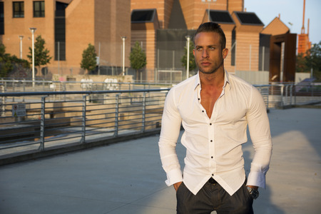 sexy guy: Handsome muscular blond man standing in city setting looking to a side, large copyspace