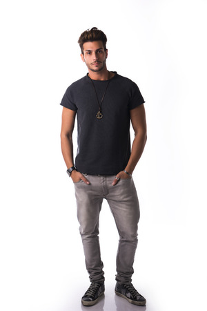 cuerpo entero: Cifra total de hombre joven y guapo confía en pie en ropa casual, mirando a la cámara aislada en blanco