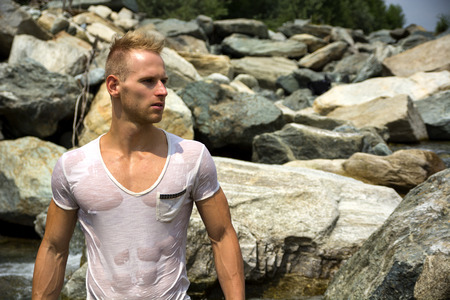 caucasian white: Handsome young muscle man standing, wearing wet white t-shirt, looking to a side. Large copyspace