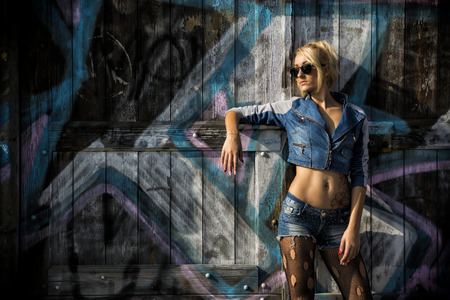 torn stockings: Young Pretty Blond Woman in Trendy Denim Fashion with Shades Leaning on Wooden Wall with Abstract Design.