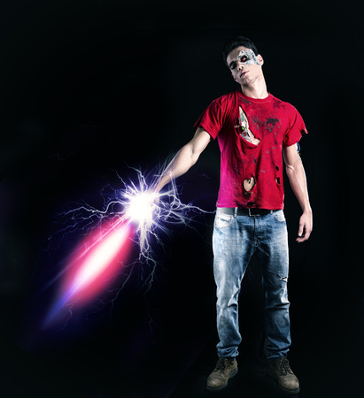 death head holding: Full Length of Young Zombie Man, Wearing Torn Red Shirt and Faded Jeans, Holding Glowing Futuristic Sword. Captured in Studio on Black Background.