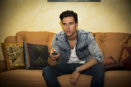 Young man sitting watching television changing the channel with the remote control photo