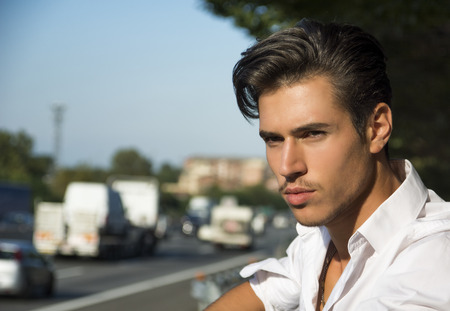 Handsome young man and road busy with cars and traffic in background photo