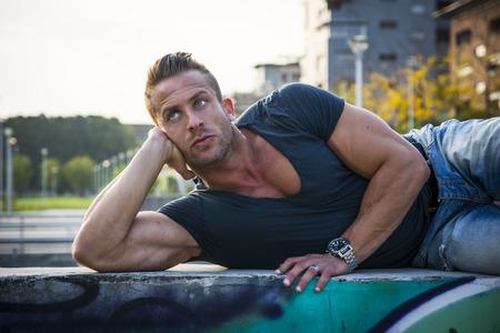 rubia ojos azules: Apuesto hombre rubio musculoso acostado en el establecimiento de la ciudad mirando a un lado