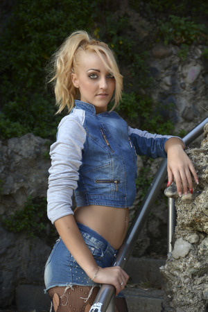 torn stockings: Young Pretty Blond Woman in Trendy Denim Fashion Outdoor Leaning on Metal Hand Railing