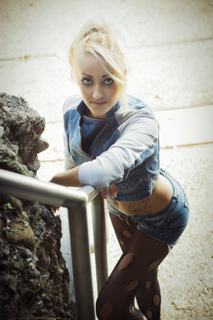 torn stockings: Young Pretty Blond Woman in Trendy Denim Fashion Leaning on Metal Hand Railing Stock Photo
