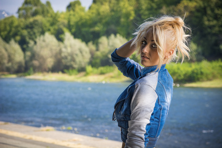 Young Pretty Blond Woman in Trendy Denim Fashion Outdoor Next to River and Park photo