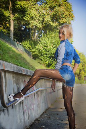 torn stockings: Young Pretty Blond Woman in Trendy Denim Fashion and Torn Stockings Stock Photo