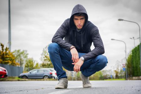 Aantrekkelijke jonge man met een capuchon en baseball cap in stad straat, kijkend naar de camera Stockfoto