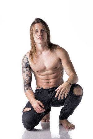 sit studio: Beautiful young long haired man shirtless, kneeling on the floor looking at camera, isolated on white
