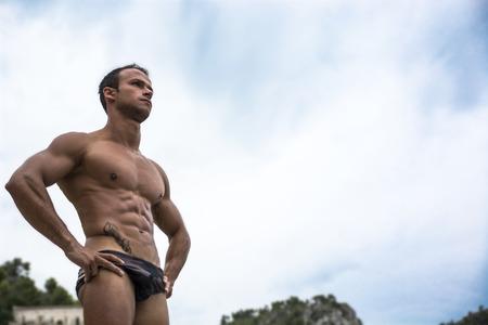 homme nu: Handsome musculaire jeune homme en maillot de bain tir� par le bas, grande copyspace sur le ciel
