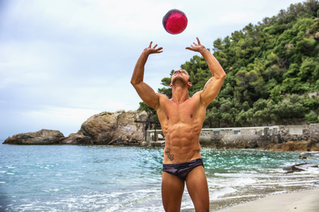 Muscular shirtless young man with volleyball playing volley on the beach