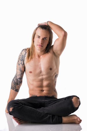 man with long hair: Beautiful young long haired man shirtless, sitting on the floor looking at camera