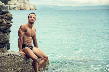 nude abs: Handsome muscular young man on the beach sitting on rocks, smiling at camera Stock Photo