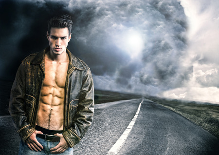 Young man walking down a road with a storm and very bad weather far away in a distance