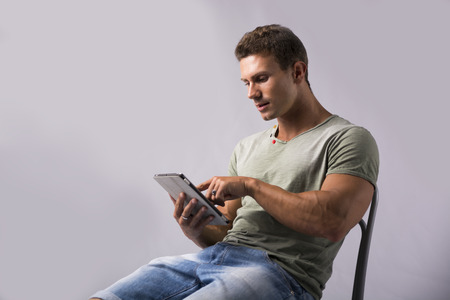 pointing device: Muscular young man sitting on chair reading from ebook device, pointing finger at screen