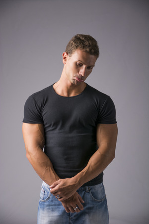 muscled: Close up Young Handsome Muscled Man in Plain Black Shirt and Blue Jeans Looking at Camera in Sad Facial Expression with Pouting Lips. Isolated on Gray Background.