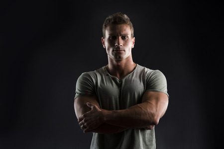 male arm: Handsome muscular fit young man on dark background looking at camera, arms crossed on his chest Stock Photo
