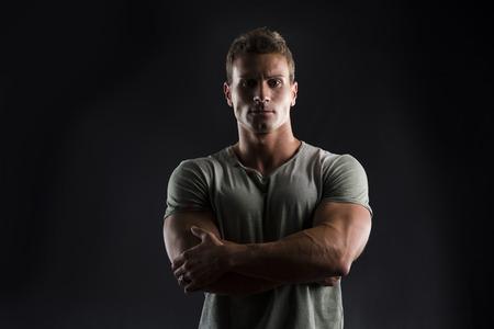 Knappe gespierde fit jonge man op een donkere achtergrond kijken camera, armen gekruist op zijn borst