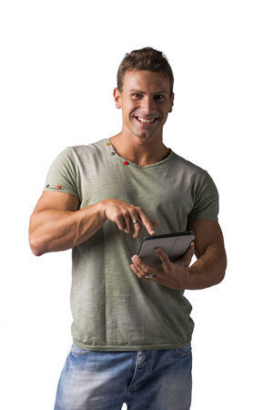 Smiling young man holding ebook reader and looking at camera, standing isolated on white background photo