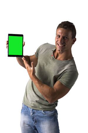 Smiling young man holding and showing ebook reader, standing isolated on white background photo