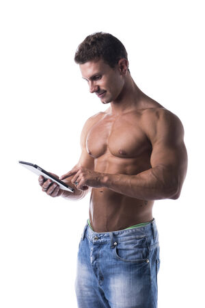 Shirtless muscular young man holding ebook reader, standing isolated on white background photo
