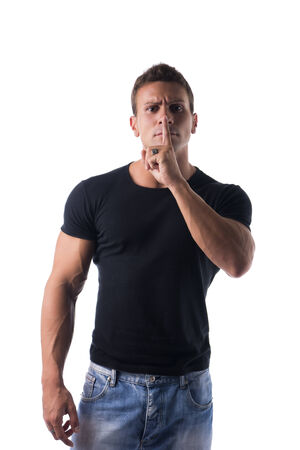 Muscular handsome young man doing shut up sign with finger on lips
