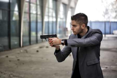 mobster: Well dressed handsome young detective or policeman or mobster standing in an urban environment aiming a firearm off to the left of the frame with a determined expression, side view Stock Photo