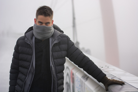 concealing: Young man in winter fashion standing outdoors in a warm overcoat and gloves with his grey scarf wound round the lower half of his face concealing his features giving the camera an enigmatic stare
