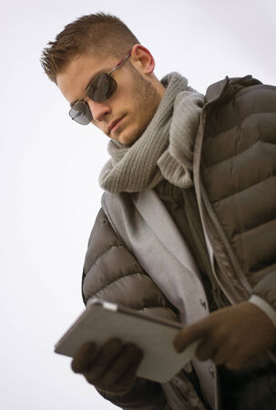 Handsome unshaven trendy man in winter fashion wearing a thick jacket, scarf and sunglasses standing looking down at a tablet computer that he is holding, low angle view photo