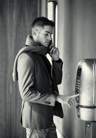 Handsome stylish young man in a tailored jacket and scarf standing using a pay phone waiting for a connection, profile view in greyscale Banque d'images