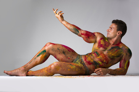Muscular young man shirtless with skin painted with Holi colors, laying down on the floor striking a pose Banco de Imagens