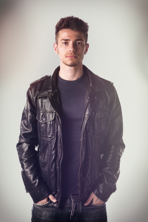 leather jacket: Attractive young man with leather jacket and hands in jeans pockets, looking at camera