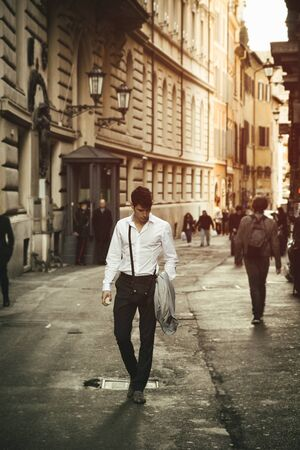 Handsome young man walking in European city street, an alley in Rome, Italy photo