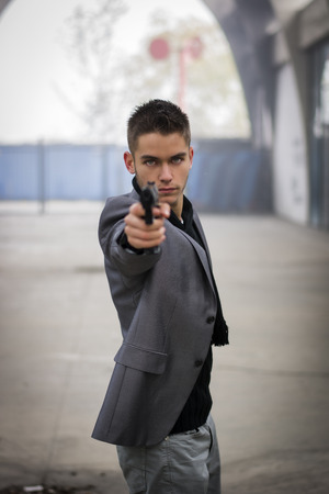 mobster: Well dressed handsome young detective or policeman or mobster standing in an urban environment aiming a firearm directly to the camera with a determined expression, front view