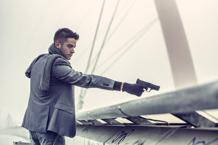 people in action: Well dressed handsome young detective or policeman or mobster standing in an urban environment aiming and firing a gun over a bridge edge