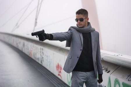 officier de police: Eh bien habill� jeune d�tective beau ou policier ou gangster debout dans un environnement urbain visant une arme � gauche