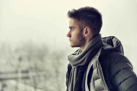 modelos hombres: Vista de perfil de hombre joven y guapo al aire libre en invierno llevaba bufanda, mirando a otro lado pensando