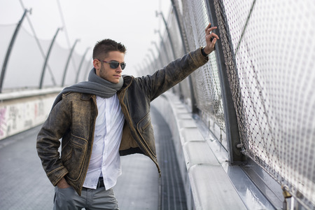 young male model: Handsome trendy young man standing on a sidewalk wearing a fashionable jacket and scarf in a relaxed confident pose looking away down the bridge