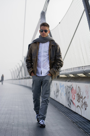 Handsome trendy young man standing on a sidewalk wearing a fashionable leather jacket and scarf in a relaxed confident pose looking at the camera photo