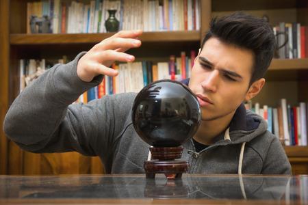 adivino: Adivino masculino joven hermoso que predecir el futuro mirando en la bola de cristal negro