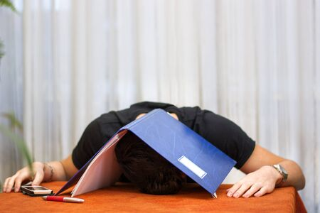 unmotivated: Tired, exhausted or despondent young man sitting at a table with a folder of paperwork over his head Stock Photo